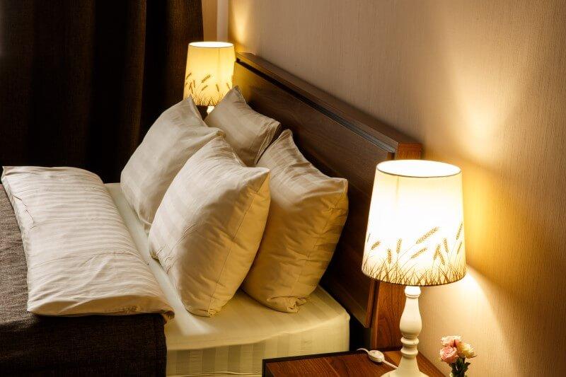 Удобные двуспальные кровати и настольные лампы на прикроватных тумбочках для размещения четырех человек