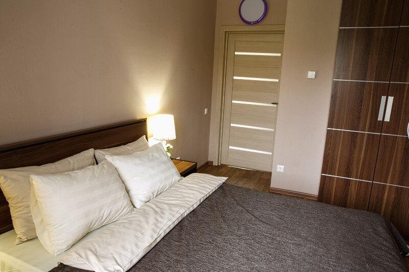 Удобные двуспальные кровати и шкафы для личных вещей в комнатах коттеджей за городом Омском