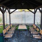 Внутри малой мангальной зоны установлены стол и стулья, имеется освещение, а снаружи беседки оборудован мангал