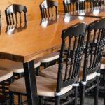 Столы из массива ясеня и черные стулья в банкетном зале Гриль хаус в Apart Hotel Линкер Парк для проведения мероприятий