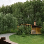 Вид с балкона коттеджа на большие мангальные зоны в окружении зеленых насаждений в летнее время